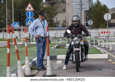 ST. PETERSBURG, RUSSIA - CIRCA AUG, 2016: Male instructor controls L-driver while she doing exercise of driving bike in parking area. Skill training motordrome. Russian driver school