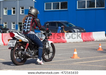 ST. PETERSBURG, RUSSIA - CIRCA AUG, 2016: Woman motorcyclist has driving test in Russian moto school for driver's license with motorcycle entitlement