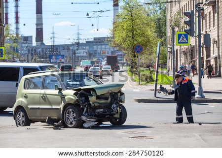 ST. PETERSBURG, RUSSIA - CIRCA MAY, 2015: Worker of municipal services removes fragments of the crashed vehicle. Accident with passing crossroads at a red light. Injured driver was hospitalized. - stock photo