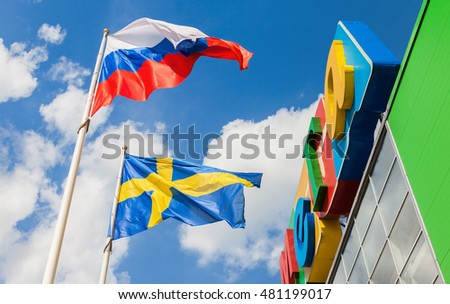ST. PETERSBURG, RUSSIA - JULY 28, 2016: Russian and Sweden flags waving against the blue sky near the shopping center Mega