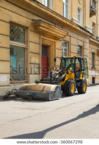 ST. PETERSBURG, RUSSIA - JULY 26, 2015: Worker sweeping machine cleans the street from the dust