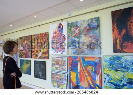 "ST. PETERSBURG, RUSSIA - JUNE 7, 2015: Spectator at first exhibition of the project ""Modern artists of the world"". Over 300 paintings and sculptures exposed in Center of modern art of Congress Palace - stock photo"