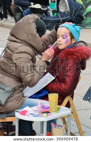 ST.PETERSBURG, RUSSIA - MARCH 13, 2016: Master body painting adorns a little girl on the street on the holiday of Maslenitsa at Moscow square