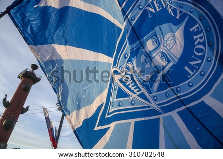 "ST.PETERSBURG, RUSSIA, MAY 25, 2015: Fan holding a flag with symbols of the football club ""Zenit"" and the fans club ""Nevsky Front"" at the center of Saint Petersburg city, Russia"