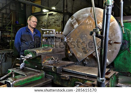 St. Petersburg, Russia - May 21, 2015: Master turner machine operator controls the processing of a large steel billets the big green lathe, Machinery equipment shop at a steel plant.