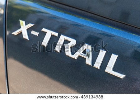 St-Petersburg, Russia - May 15, 2016: Nissan  X-Trail SUV car logo, closeup photo with selective focus - stock photo