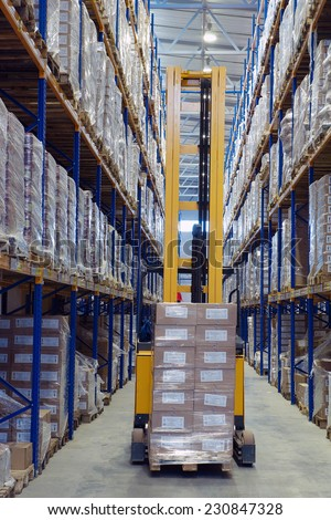 St. Petersburg, Russia - November 21, 2008: Forklift pallet truck traveling along the narrow aisle goods warehouse, with load palletising. A fork lift truck moves stacked pallets. - stock photo
