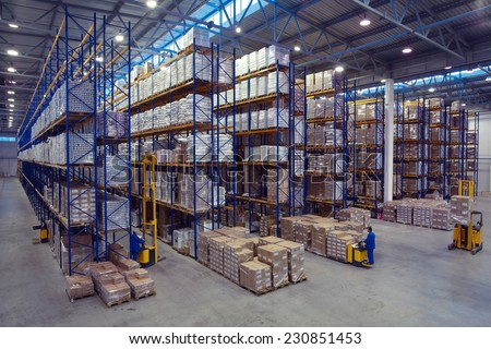 St. Petersburg, Russia - November 21, 2008: Forklift palletiser carrying palletising on the territory of  warehouse. The interior of a large goods warehouse with shelves of pallet rack system storage.