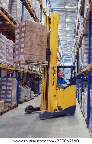 St. Petersburg, Russia - November 21, 2008: Yellow Forklift pallet truck lifts the pallet in the narrow aisle warehouse. Forklift raises palletising on top shelf of the rack. - stock photo