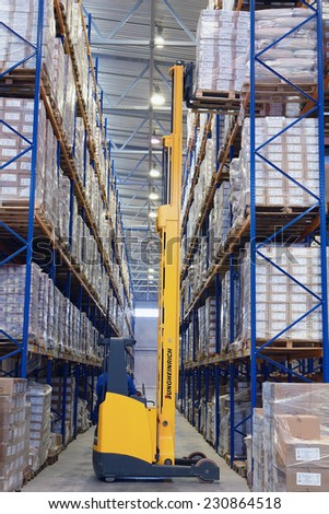 St. Petersburg, Russia - November 21, 2008: Yellow pedestrian stacker lifts pallet with boxes on shelves. Forklift pallet truck lifts pallet in narrow aisle warehouse. Fork lift truck with raised fork - stock photo