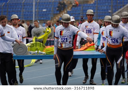 ST. PETERSBURG, RUSSIA - SEPTEMBER 9, 2015: Team Germany bring fire hoses before competitions in combat deployment during XI World Championship in Fire and Rescue Sport - stock photo