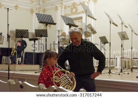 ST. PETERSBURG, RUSSIA - SEPTEMBER 7, 2015: Virtuoso horn player Hermann Baumann (right) and a girl with French horn on the rehearsal during the International festival of French horn - stock photo