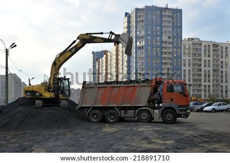 St. Petersburg, Russia - 19 SEPTEMBER: yellow excavator loads ib a red truck black gravel on SEPTEMBER 19, 2014, St. Petersburg, Russia  - stock photo