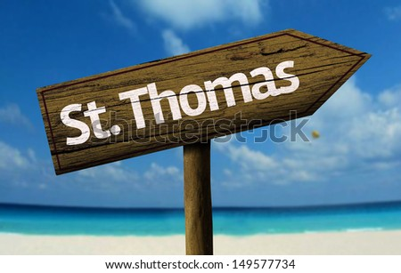 St. Thomas wooden sign with a beach on background   - stock photo