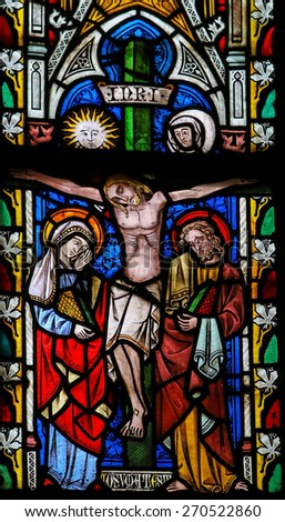 ST TRUIDEN, BELGIUM - APRIL 21, 2013: Stained glass window depicting Jesus on the Cross, in the Cathedral of Saint Truiden in Limburg, Belgium. - stock photo