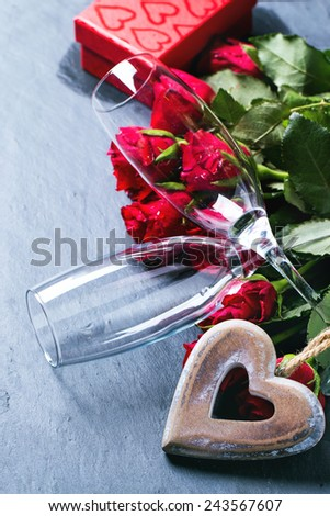 St Valentine greeting card with red roses, heart and champagne glasses at black stone background. See series