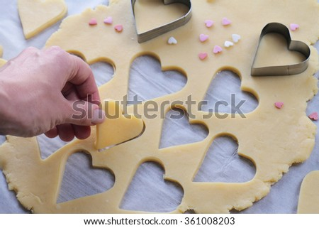 St. valentine's day cookies. Woman making heart shaped cookies close up.
