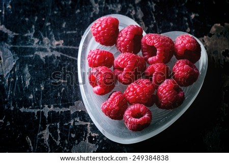 st Valentine's greeting card with fresh raspberry in heart shaped plate over black wooden background. Top view - stock photo