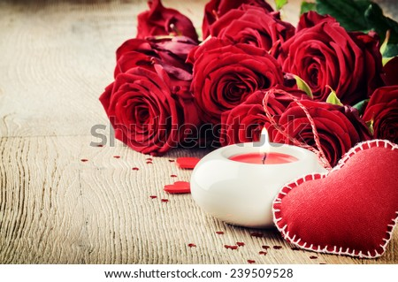 St Valentine's setting with bouquet of red roses and candle - stock photo
