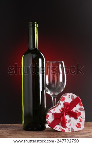 St Valentine's setting with present and red wine gift - stock photo