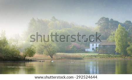 Stable Hill Farm at Derwent Water, Lake District, UK, on a misty spring morning, with ducks, swans and reflections of the house and trees in the water.  - stock photo