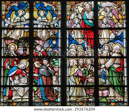 STABROEK, BELGIUM - JUNE 27, 2015: Stained glass window depicting a Nativity Scene at Christmas and the Resurrected Christ in the Church of Stabroek, Belgium. - stock photo