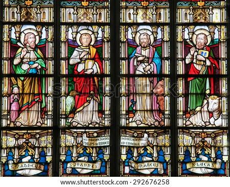 STABROEK, BELGIUM - JUNE 27, 2015: Stained glass window depicting the Four Evangelists, Saint Matthew, Saint John, Saint Mark and Saint Luke, in the Church of Stabroek, Belgium. - stock photo