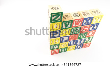 Stack and aligned alphabet wooden block letter set from A to Z. Concept of basic education. Isolated on white background. Slightly de-focused and close-up shot. Copy space.