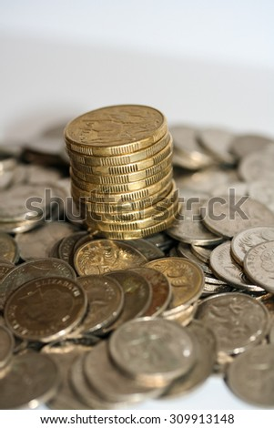 Stack and column of gold dollar coins on pile of silver five cent pieces. It all adds up concept. - stock photo