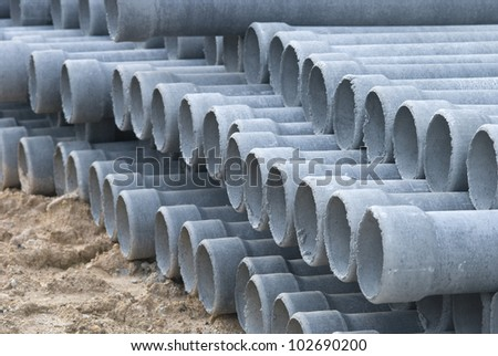 Stack concrete drainage pipe in construction site - stock photo