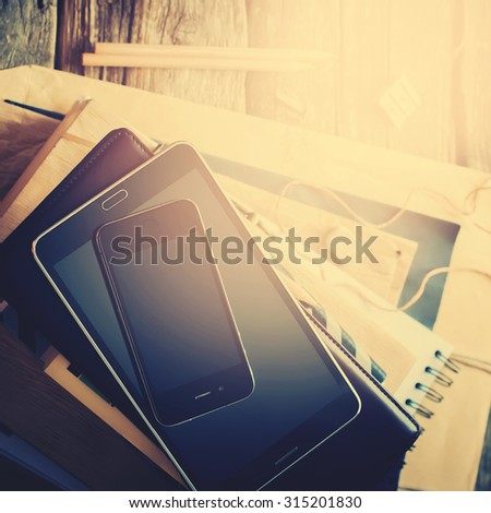 Stack of Accessories and Digital Gadgets for Business Men on Home Wooden Table. Tablet pc, phone, paper, different stuff. Top view. Toned image - stock photo