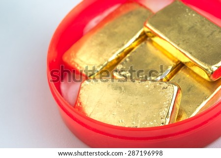 Stack of actual smallest gold bars commonly sold in Thailand in red container round box over white table. Each bar is 96.5% purity gold which is roughly equal to 99.5% purity 2.527 troy ounce. - stock photo