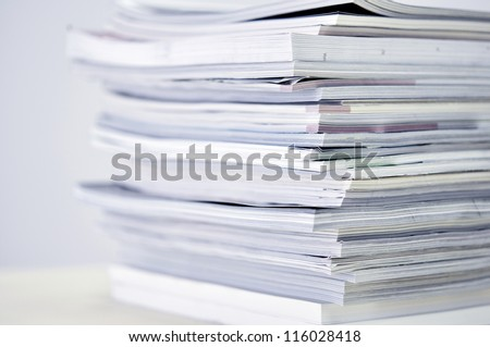 Stack of ?agazines with selective focus on foreground edge - stock photo