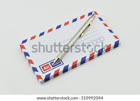 Stack of air mail envelopes and pen on white background