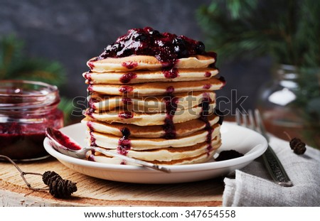 Stack of american pancakes or fritters with strawberry and blueberry jam in white plate on wooden rustic table decorated Christmas tree, delicious dessert for breakfast in winter, vintage style - stock photo