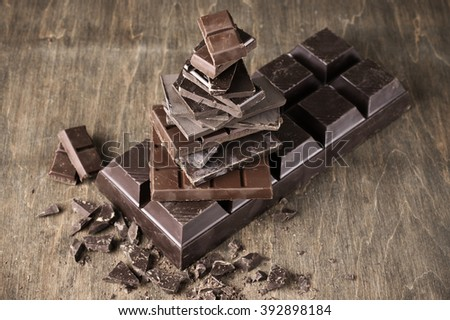 Stack of assorted broken chocolate and dark chocolate bar on vintage wooden background. - stock photo