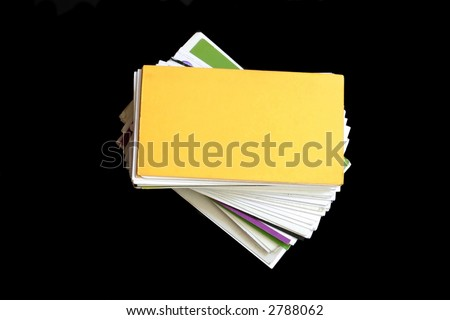 stack of assorted business cards over black background - stock photo