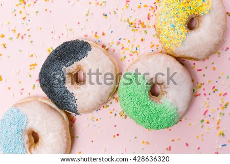 Stack of assorted donuts on a pink background - stock photo