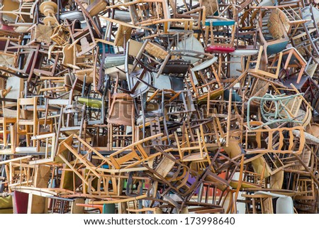 Stack of assorted metal and wooden chairs in random disarray, full frame furniture background image - stock photo