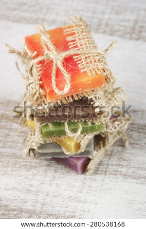 Stack of assorted natural soaps on vintage wood. Shallow DOF, focus on top soap. - stock photo