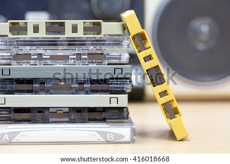 Stack of audio cassettes with one cassette player background