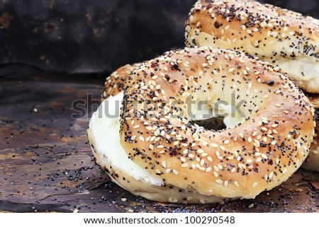 Stack of bagels and cream cheese against a rustic slate background. - stock photo