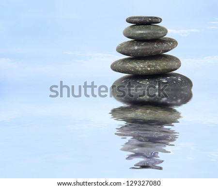 stack of balanced zen stones in water on blue sky background - stock photo