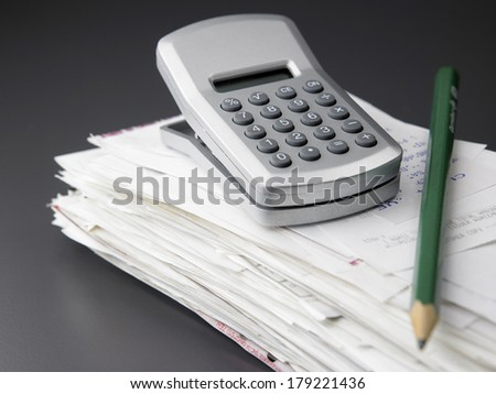 stack of  bill and calculator