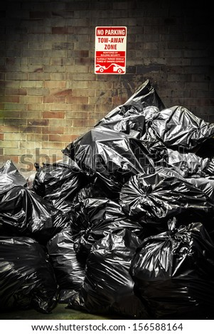 Stack of black plastic trash bags in urban alley  - stock photo