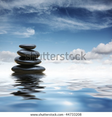Stack of black zen pebble stones reflecting in water over blue sky background - stock photo