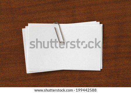 Stack of Blank Cards with paper Clip. on Wood Desk - stock photo