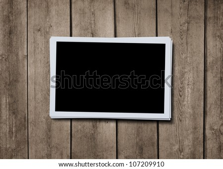 Stack of blank photographs at grunge wooden background with clipping path for the inside of the photo - stock photo