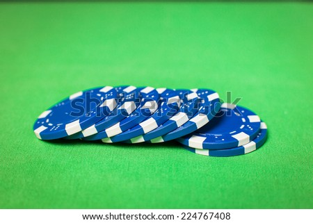 stack of blue poker chips on a green table - stock photo
