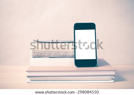 stack of book and smart phone on wood background vintage style